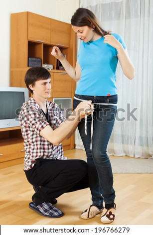 Guy measuring  thigh of girlfriend with measuring tape at home  - stock photo