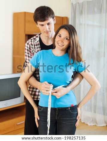 Guy measuring waist of girl with measuring tape at home - stock photo