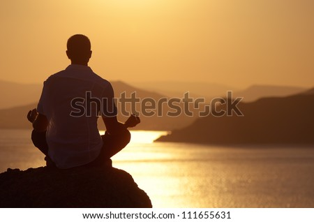 Guy meditating at sunset sitting on a rock by the sea - stock photo