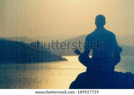 Guy meditating at sunset sitting on a rock by the sea. Filtered image: vintage, grunge and texture effects - stock photo