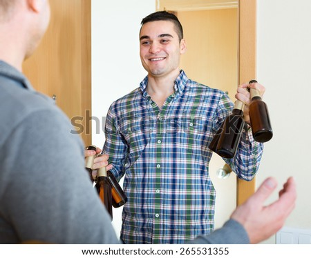 Guy meeting smiling buddy 35-40 years old with beer bottles at doorway - stock photo
