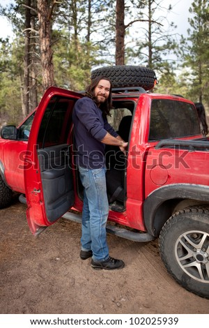 Guy on a camping trip by his truck - stock photo