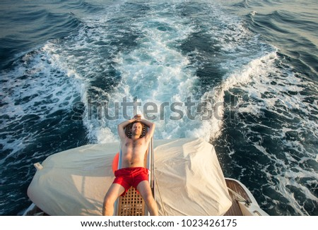Guy on a yacht in the summer, Rest on the yacht,  Sits on the stern of the yacht