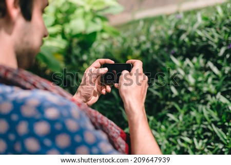 Guy playing games on his smartphone - stock photo