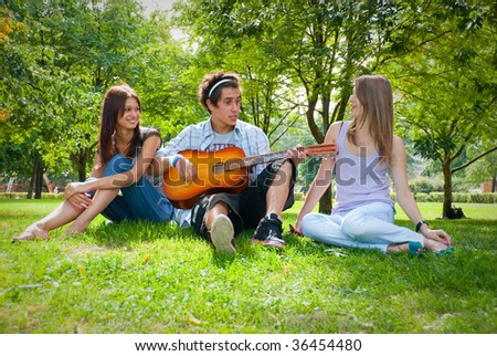 Guy playing guitar in the park, next to him sat two beautiful girls - stock photo