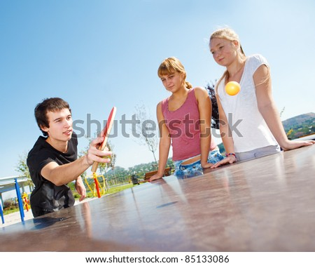 Guy playing ping pong, his friends watching