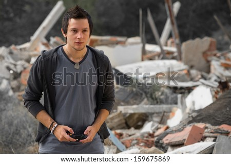 Guy playing with his console surrounded by rubble, a concept - stock photo