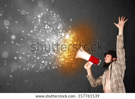 Guy shouting into megaphone and glowing energy particles explode concept - stock photo