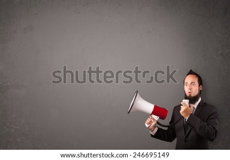 Guy shouting into megaphone on copy space background - stock photo