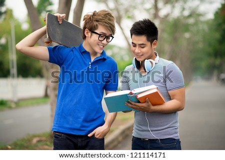 Guy showing the most interesting part of the book to his skater friend - stock photo
