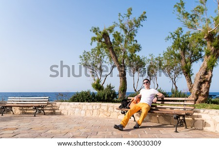guy sitting on a bench near the sea