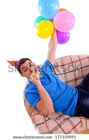 Guy sitting on the couch with a cap and balloons and whistling isolated - stock photo