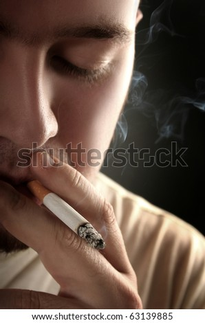 guy smoking cigarette on dark background - stock photo