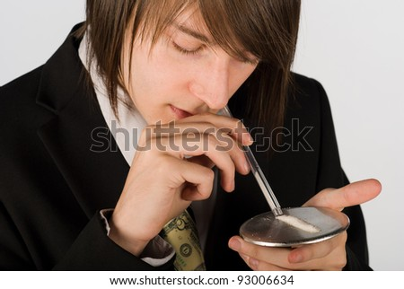 Guy snorting a line of cocaint through an empty pen - stock photo