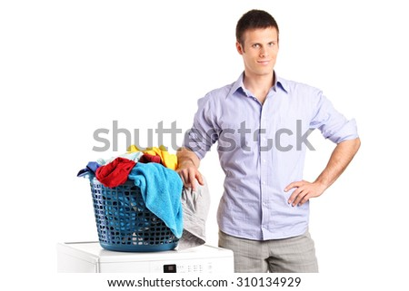 Guy standing by a washing machine with a laundry basket on it isolated on white background