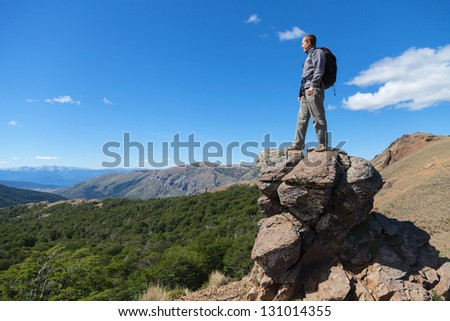 Guy standing on a rock in the mountains
