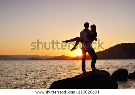 Guy standing on a rock near the sea and holding the girl in his arms - stock photo