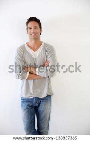 Guy standing on white background with arms crossed - stock photo