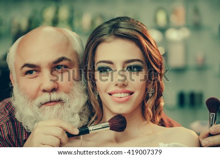 Guy stylist with long white beard and pretty woman in beauty salon holding makeup brushes