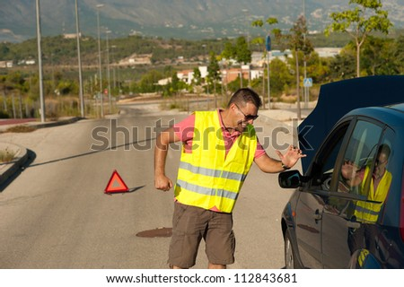 Guy truly hating his car after a breakdown - stock photo
