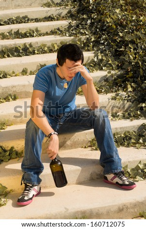Guy trying to drown his worries with alcohol - stock photo