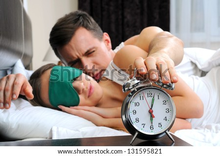 guy turning off alarm clock - stock photo