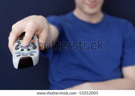 Guy watching tv with remote - stock photo