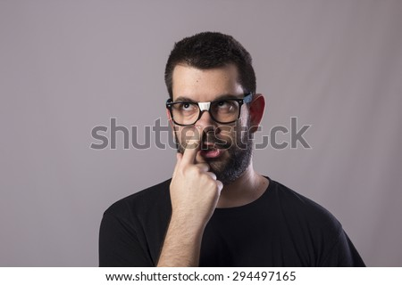 Guy wearing glasses with finger on nose