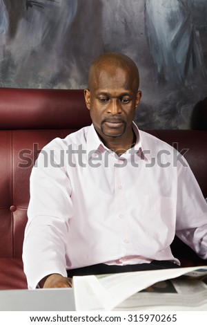 Guy wearing pink shirt reading newspaper while sitting at the table on leather sofa - stock photo