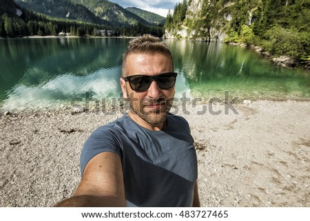 guy who snaps a selfie in front of a lake in the mountains