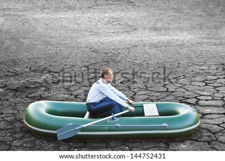 Guy will rows home for shore in paddle powered row boat businessman in boat rocks looks bright future symbol crisis stagnation losses braking difficulties environmental disaster water scarcity drought - stock photo