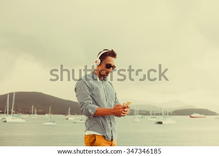 guy with a beard in sunglasses shirt and shorts listening ,music in headphones,Young man wearing white blank t-shirt and blue jeans, standing on the street,amazing casual style,vintage style - stock photo