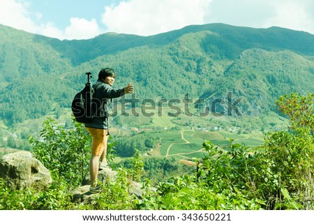 Guy with a travel backpack and tripod on the top of a boulder - stock photo