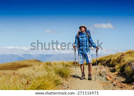 Guy with a travel backpack on the hiking trail. New Zealand. Kepler trek - stock photo