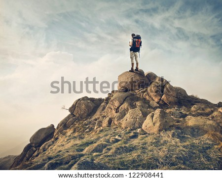 Guy with a travel backpack on the top of a boulder - stock photo