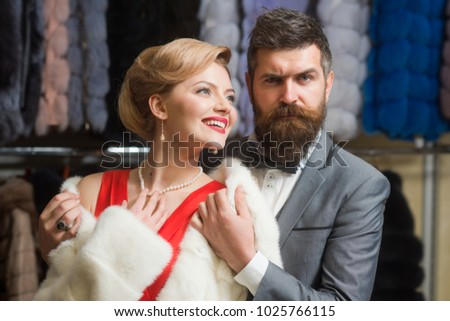 Guy with beard and woman buy furry coat. Man and girl with happy faces hold furry coats on clothes rack background. Rich fashion concept. Couple in love tries expensive grey and white sable overcoats