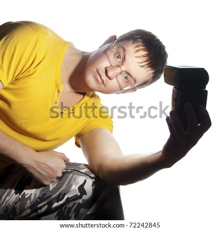 Guy with glasses and yellow shirt. Illuminates himself flash in his left hand. Isolated on a white background.