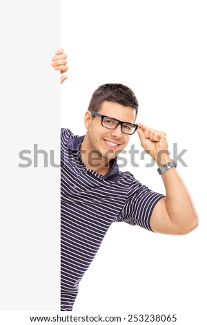 Guy with glasses posing behind blank panel isolated on white background - stock photo