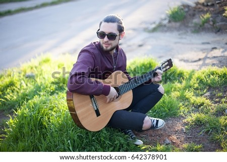 guy with guitar sits on the ground