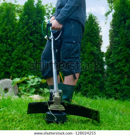 Guy with lawn mower in front of back yard - stock photo