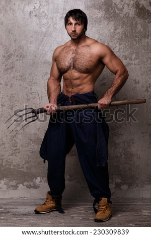 Guy with perfect body holding pitchfork