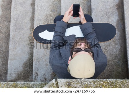 Guy with skateboard and smartphone sitting on the stairs. - stock photo