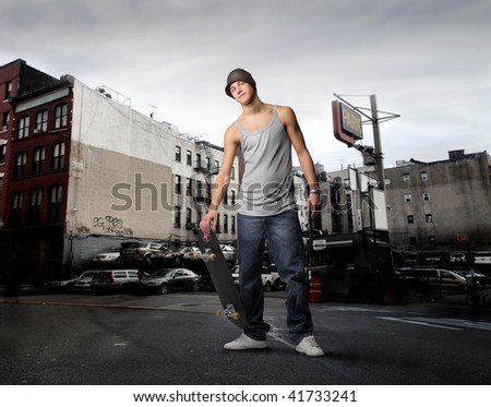 guy with skateboard in a city street - stock photo
