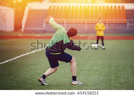 Guy with the team is throwing, throwing and catching with flying disk at the sports stadium. Concept of the game is active and mobile in summer. Sunny highlight.
