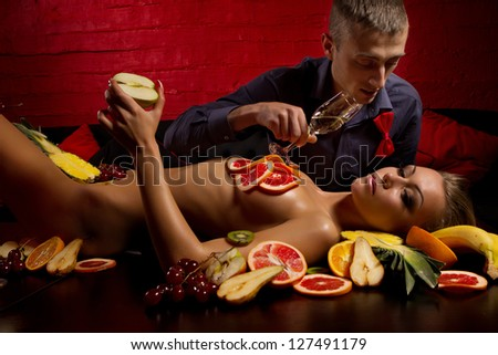 Guy with woman decorated  by fruits - stock photo
