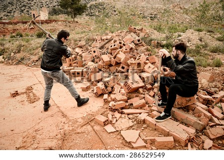 Guy working hard with a bystander doing nothing, a concept - stock photo