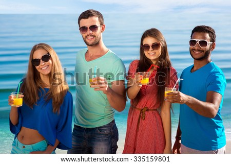 Guys and girls on the background of the sea. Relax on the islands. Travel to the islands. Luxury vacation.Friends relaxing in the seaside resort. - stock photo