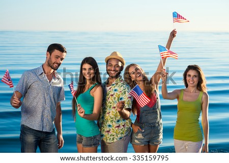 Guys and girls with American flags on the beach. Patriots of America. Young people having fun. - stock photo