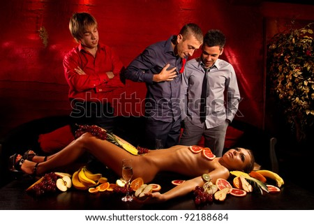 Guys having fun with woman decorated  by fruits - stock photo