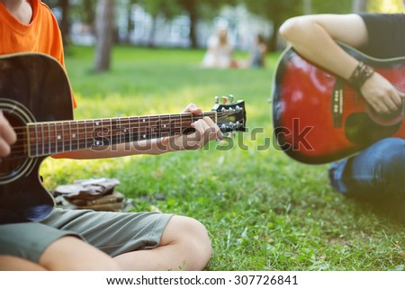 Guys Play Guitars in City Park Outdoor - stock photo